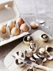 Close-up view of fresh raw mushrooms on cutting board with knife and eggs in egg box — Stock Photo
