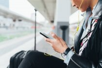 Woman on train platform using smartphone — Stock Photo