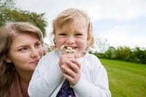 Mère et fille dans le champ et fille tenant marguerites — Photo de stock