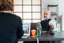 Колегами в офісі говорити і використовуючи ноутбуки — стокове фото