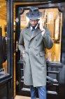 Cliente masculino em casaco e trilby fora alfaiates loja — Fotografia de Stock