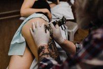 Крупный план татуировки татуировки бедра молодой женщины — стоковое фото