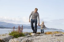 Hijo de hombre y niño paseando por el fiordo, Aure, más og Romsdal, Noruega - foto de stock