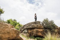 Distant view of Young female tourist looking out from rock at Bourkes Potholes, Mpumalanga, South Africa — Stock Photo