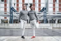 Les jeunes jumeaux masculins s'entraînent et s'étirent ensemble — Photo de stock