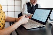 Женщина с помощью смартфона и ноутбука на рабочем столе — стоковое фото