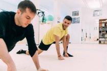 Homens na Academia fazendo exercícios de alongamento — Fotografia de Stock