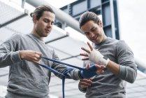 Boxer maschili identici che fasciano le mani con involucri a mano — Foto stock