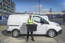 Senior-Lieferfahrer mit Plastikbox in der Nähe von Elektro-Transporter — Stockfoto