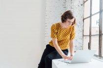 Бізнес-леді сидячи на підвіконні і використання ноутбука — стокове фото