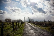 Rural road with fence and clouds in sky — Stock Photo