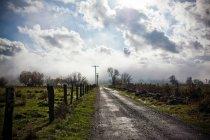 Сельская дорога с забором и облаками в небе — стоковое фото