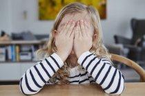 Портрет молодой девушки за столом, закрывающей лицо руками — стоковое фото