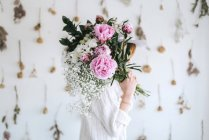 Woman covering face bunch of flowers — Stock Photo