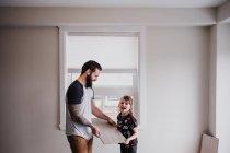 Chica ayudando padre celebración piso de baldosas - foto de stock
