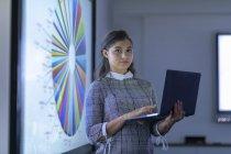 Retrato de jovem empresária com laptop e telas interativas com gráficos — Fotografia de Stock