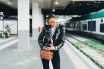 Mulher com smartphone em pé perto da plataforma de trem — Fotografia de Stock