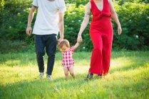 Couple avec bébé fille faisant les premiers pas dans le jardin — Photo de stock