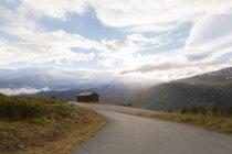 Iluminado pelo sol de estradas rurais na paisagem de montanha, Parque Nacional de Jotunheimen, Lom, Oppland, Noruega — Fotografia de Stock