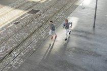 Young male twins running along sidewalk — Stock Photo