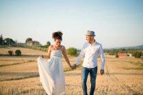 Couple marchant à travers le champ avec la main — Photo de stock