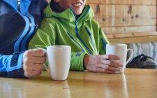 Отец и сын делают перерыв на кофе в бревенчатой хижине, Hintertux, Тироль, Австрия — стоковое фото