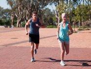 Casal jovem correndo em sportswear ao ar livre durante o dia — Fotografia de Stock