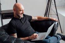 Mann im Sessel mit Laptop und lächelnd — Stockfoto