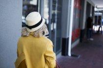 Vista trasera de la mujer en sombrero caminando por el pasillo - foto de stock