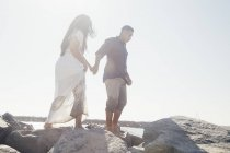 Couple standing on coastal rock, low angle view, Seal Beach, California, USA — Stock Photo