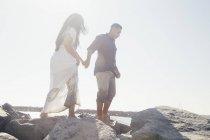 Casal em pé na rocha costeira, vista de baixo ângulo, Seal Beach, Califórnia, EUA — Fotografia de Stock