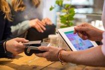 Cliente donna in negozio, pagamento merce con carta di credito su macchina di pagamento contactless, sezione centrale, primo piano — Foto stock