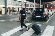 Donna che cammina con valigia a ruote e parla su smartphone — Foto stock