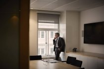 Geschäftsmann im Büro telefoniert mit Smartphone — Stockfoto