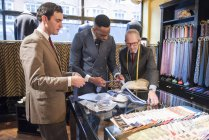 Tailors and customer choosing shirt and tie in tailors shop — Stock Photo