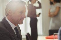 Вид збоку бізнесмена в офісі розмовляти з колегою — стокове фото