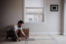 Vista laterale dell'uomo installazione di piastrelle del pavimento — Foto stock