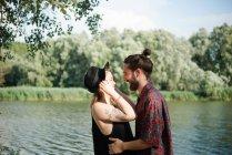 Coppia giovane che si sorride in riva al lago, Toscana, Italia — Foto stock