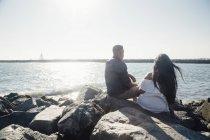 Пара, сидя на прибрежных скалах, глядя на вид, вид сзади — стоковое фото