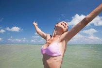 Mulher jovem feliz no mar com os braços abertos — Fotografia de Stock