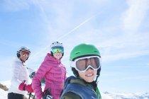 Мать с дочерью и сыном на лыжном празднике, улыбаясь на камеру — стоковое фото