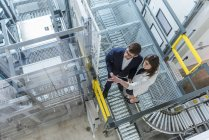 Elevated view of two colleagues in industrial building — Stock Photo
