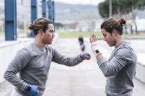 Twin boxers practicing punches outdoors — Stock Photo