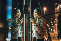Mulher segurando no exterior smartphone através da construção de — Fotografia de Stock