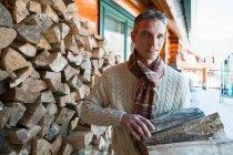 Retrato de homem segurando logs perto da casa — Fotografia de Stock