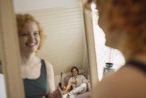 Spiegelbild der Frau im Loft-Zimmer junge Mann lächelte — Stockfoto