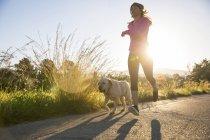 Молода жінка працює по сільській дорозі з собакою — стокове фото