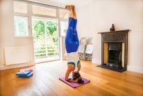 Mulher de pé na cabeça na posição de ioga — Fotografia de Stock