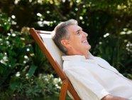 Ritratto di uomo che si siede sulla sedia a sdraio — Foto stock