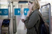 Mulher usando telefone celular pela barreira do bilhete, Cape Town, África do Sul — Fotografia de Stock